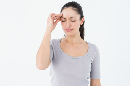 Brunette suffering from migraine on white background