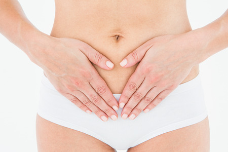 cramps: Fit woman with stomach pain on white background