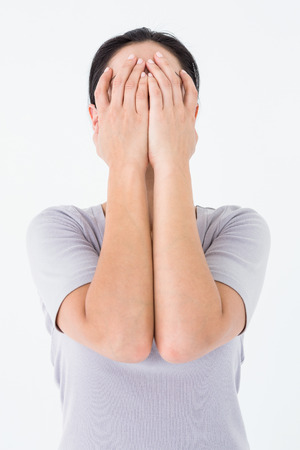 desolaci�n: Mujer triste que oculta su cara en el fondo blanco Foto de archivo