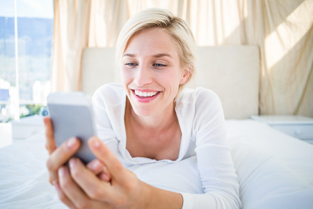 Smiling blonde woman lying on the bed and texting with her mobile phone in the bedroom