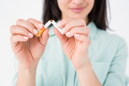 Smiling woman snapping cigarette in half on white background Stock Photo