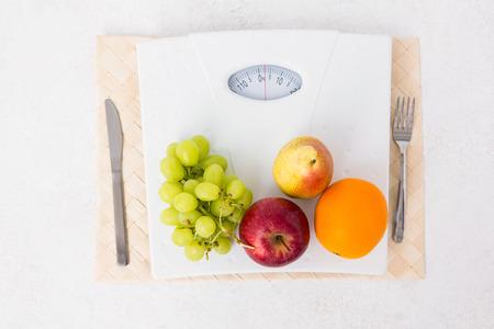 weighing scales: Bilance con frutta su sfondo bianco Archivio Fotografico