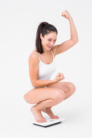 weighing scales: Beautiful woman cheering on weighing scales on white background