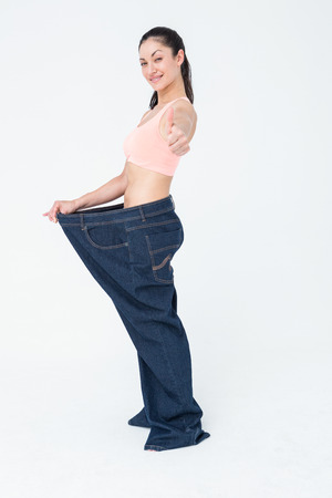 losing weight: Woman showing her waist after losing weight on white background