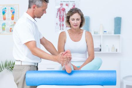 医師の診療所で彼の患者の足を調べる