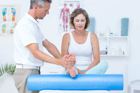 alternative therapies: Doctor examining his patients leg in medical office