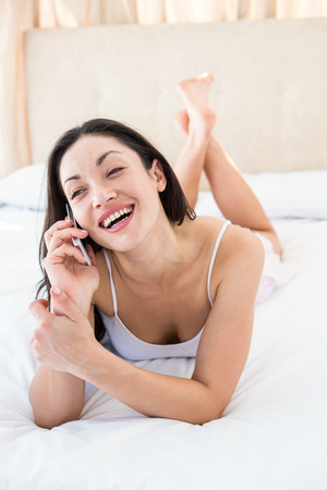 Pretty brunette calling on bed at home Stock Photo