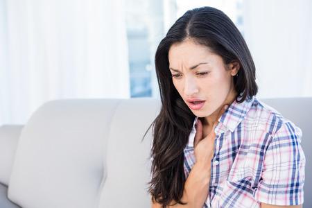 tosiendo: Pretty morena tos en el sofá en casa, en la sala de estar