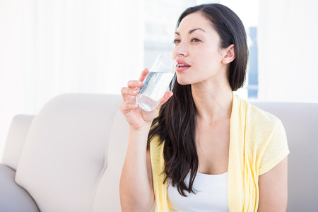 Pretty brunette drinking glass of water on couch in the living-room