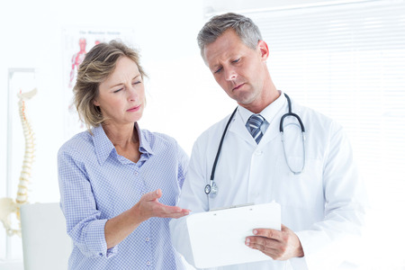 Doctor showing his notes to his patient in medical office photo