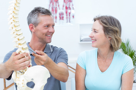 chiropractor: Physiotherapist showing spine model to his patient in medical office