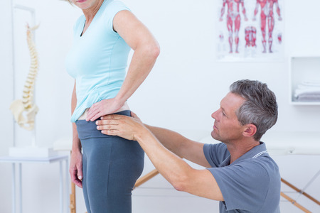 posture correction: Physiotherapist examining his patient back in medical office Stock Photo