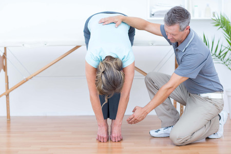 retraining: Physiotherapist helping his patient stretching in medical office Stock Photo