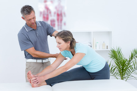 Physiotherapist helping his patient stretching in medical office photo