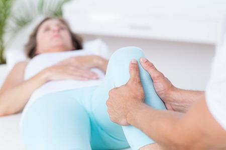 fisioterapia: Fisioterapeuta haciendo masaje de piernas a su paciente en el consultorio médico