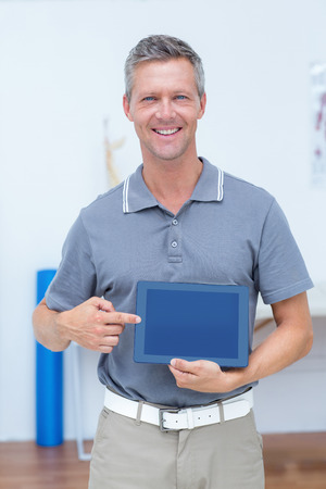naprapathy: Smiling doctor showing digital tablet in medical office Stock Photo