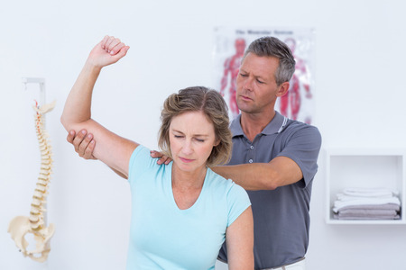 physical pressure: Doctor examining his patient arm in medical office Stock Photo
