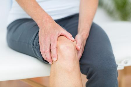 dolor de rodilla: Mujer que tiene dolor de rodilla en el consultorio m�dico Foto de archivo