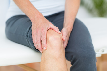 Woman having knee pain in medical office Stock Photo