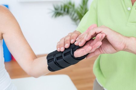 orthopaedic: Doctor examining his patients wrist in medical office