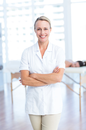 Physiotherapist smiling at camera arms crossed in medical office Stock Photo