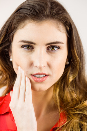 Pretty brunette with a toothache on white background Stock Photo