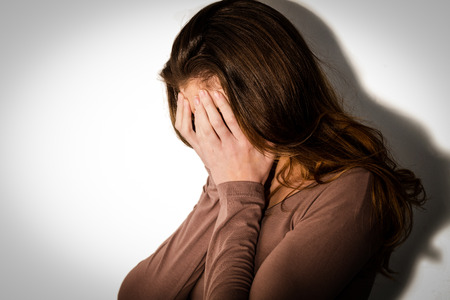 bleakness: Depressed woman with head in hands on white background Stock Photo