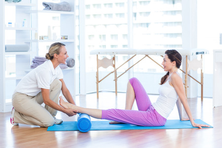 Trainer working with woman on exercise mat in medical office
