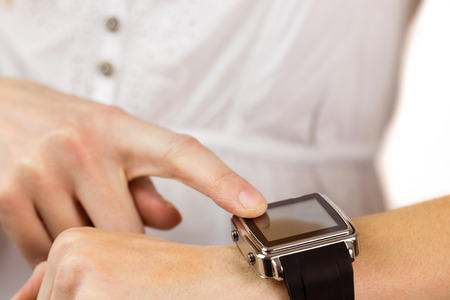 cut wrist: Woman using her smart watch on white background Stock Photo
