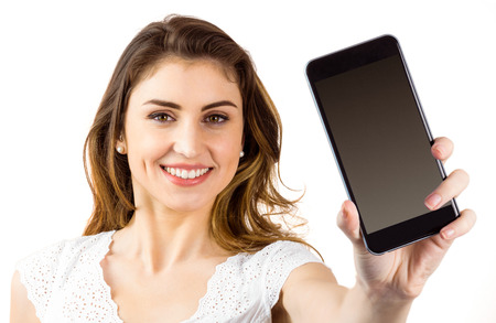 wavy hair: Pretty brunette showing smartphone on white background