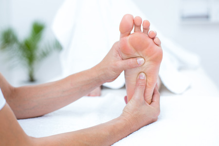 physiotherapist: Physiotherapist doing foot massage in medical office Stock Photo