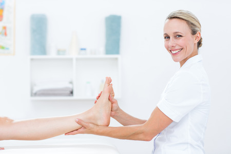 Physiotherapist doing foot massage in medical office Standard-Bild