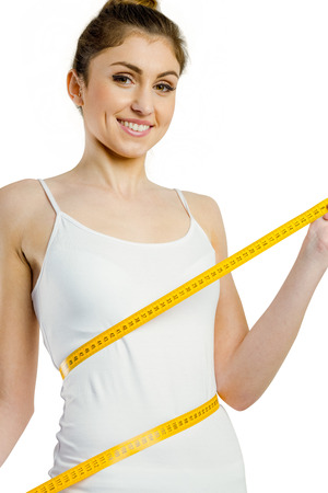 body concern: Slim woman measuring her waist on white background
