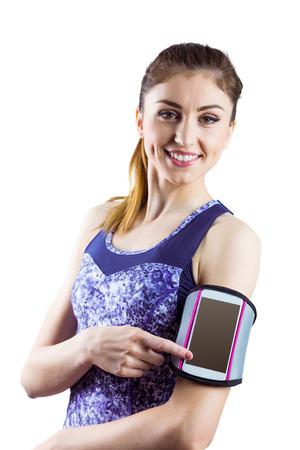 armband: Donna adatta utilizzando smartphone in fascia su sfondo bianco Archivio Fotografico