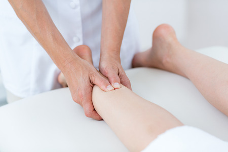 massage jambe: Physiotherapist doing leg massage in medical office Banque d'images
