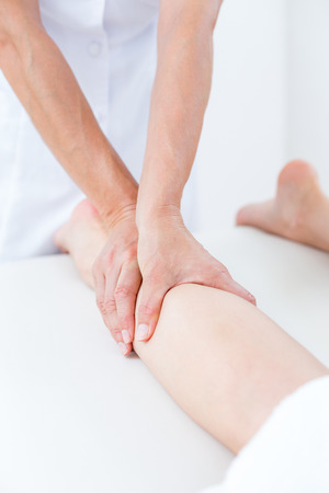 leg calf injury: Physiotherapist doing leg massage in medical office Stock Photo