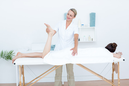 physiotherapist: Physiotherapist doing leg massage in medical office Stock Photo