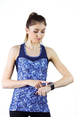 athletic wear: Fit brunette using her smartwatch on white background Stock Photo