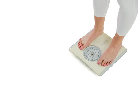 body concern: Woman standing on scales on white background Stock Photo