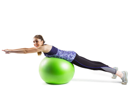 body toning: Fit woman exercising on exercise ball on white background
