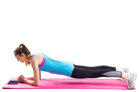 plank position: Fit woman doing plank on mat on white background Stock Photo