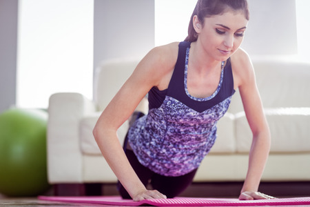 plank position: Fit woman doing press up on exercise mat at home in the living room