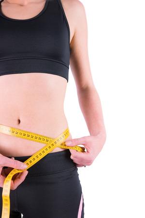 silhouette feminine: mince femme mesurant la taille avec un ruban � mesurer sur fond blanc