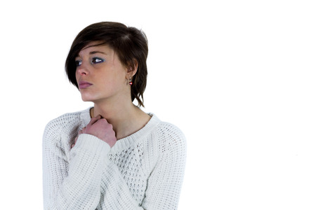 unhappiness: Sad pretty brunette thinking with arms crossed on white background