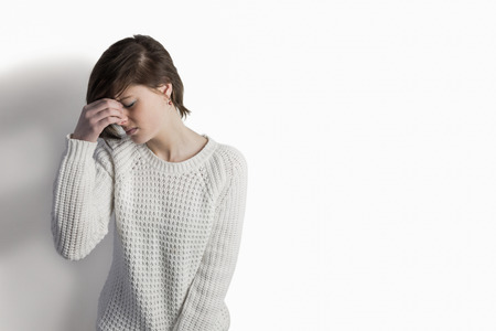 dreariness: Sad pretty brunette leaning against wall on white background