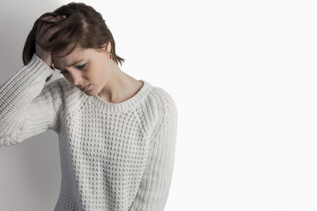 wistfulness: Sad pretty brunette leaning against wall on white background