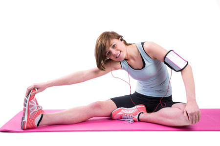 hamstring: Pretty brunette doing the hamstring stretch on exercise mat on white background