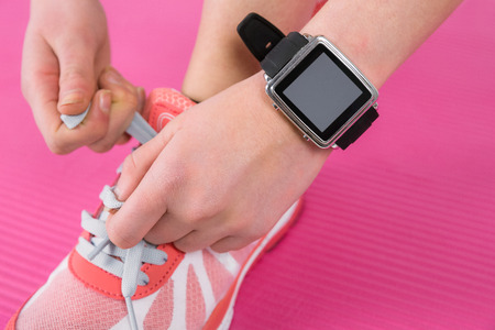 athletic wear: Woman tying her laces of sport shoes on pink exercise mat
