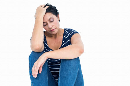 desolaci�n: Mujer infeliz que se sienta en el suelo sobre fondo blanco