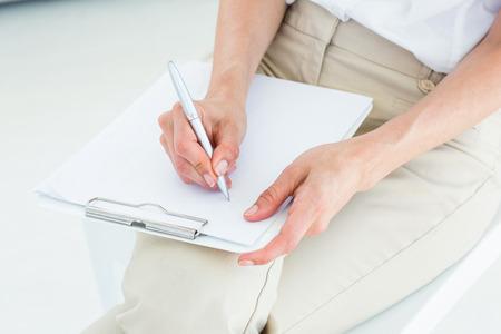 taking note: Therapist prendere appunti su sfondo bianco